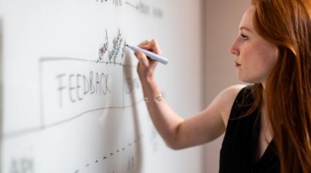 woman-in-black-sleeveless-top-writing-on-whiteboard HD